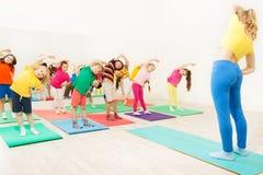 Entraîneur de gymnastique faisant le recourbement en longueur avec des enfants Images libres de droits