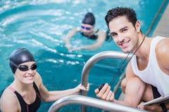 Entraîneur de sourire montrant le chronomètre au nageur image libre de droits