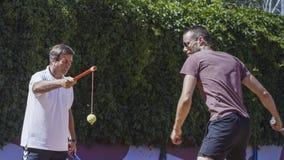 Entraîneur de tennis travaillant avec l'homme sur la cour photos stock