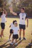 Entraîneur et écolière donnant la haute cinq entre eux pendant la concurrence Photo stock