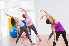 Entraîneur et amis féminins faisant étirant l'exercice Photographie stock