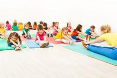 Entraîneur et enfants faisant l'échauffement pendant la gymnastique Image libre de droits