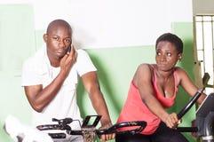 Entraîneur et jeune femme sur des vélos d'exercice dans le gymnase photographie stock libre de droits