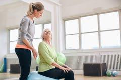 Entraîneur féminin aidant l'exercice supérieur de femme Photos stock