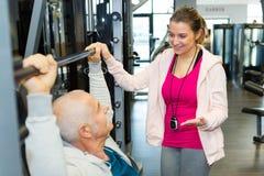 Entraîneur féminin aidant l'homme supérieur dans le poids de levage au gymnase Photographie stock