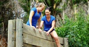 Entraîneur féminin aidant la femme convenable pour s'élever au-dessus du mur en bois pendant le parcours du combattant 4k banque de vidéos