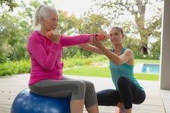 Entraîneur féminin aidant la femme supérieure active pour s'exercer avec des haltères dans le porche photo libre de droits