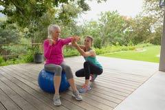Entraîneur féminin aidant la femme supérieure active pour s'exercer avec des haltères dans le porche photos libres de droits