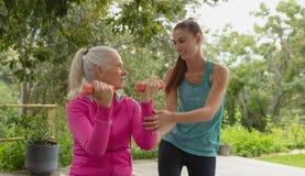 Entraîneur féminin aidant la femme supérieure active pour s'exercer avec l'haltère dans le porche photos libres de droits