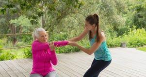 Entraîneur féminin aidant la femme supérieure active pour s'exercer dans le porche photos stock
