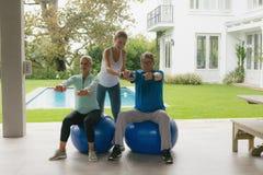 Entraîneur féminin aidant les couples supérieurs actifs pour s'exercer avec l'haltère dans le porche images stock