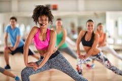 Entraîneur féminin avec le casque faisant des exercices avec le groupe de forme physique image libre de droits