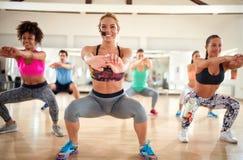 Entraîneur féminin avec le casque faisant des postures accroupies avec le groupe de forme physique photos stock