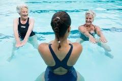 Entraîneur féminin avec les femmes supérieures s'exerçant dans la piscine image stock