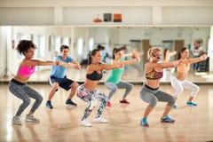 Entraîneur féminin avec les jeunes faisant des exercices photos stock