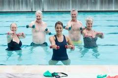 Entraîneur féminin avec les nageurs supérieurs s'exerçant dans la piscine Image stock