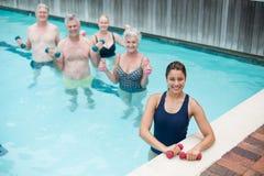 Entraîneur féminin avec les nageurs supérieurs se tenant dans la piscine Image libre de droits