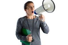 Entraîneur féminin de rugby annonçant sur le mégaphone Photographie stock libre de droits