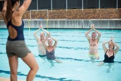 Entraîneur féminin de yoga aidant les nageurs supérieurs au poolside photographie stock