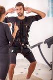 Entraîneur féminin donnant à homme SME d'électro exercis musculaires de stimulation Image libre de droits