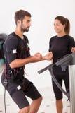 Entraîneur féminin donnant à homme SME d'électro exercis musculaires de stimulation Photos stock