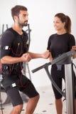 Entraîneur féminin donnant à homme SME l'électro exerci musculaire de stimulation Photo stock