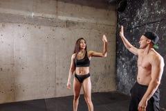 Entraîneur féminin donnant la haute cinq avec l'homme musculaire Photo libre de droits