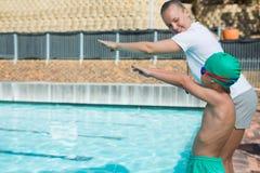Entraîneur féminin formant un garçon pour plonger dans la piscine photo stock