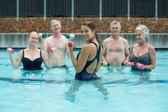 Entraîneur féminin fort avec les nageurs supérieurs dans la piscine Photo libre de droits