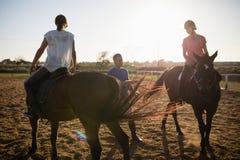 Entraîneur guidant les amis féminins dans le cheval d'équitation Images stock