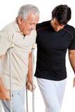 Entraîneur Helping Senior Man avec des béquilles Photographie stock