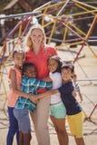Entraîneur heureux et écoliers se tenant ensemble au terrain de jeu d'école Photos stock