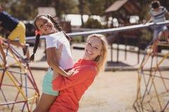 Entraîneur heureux et fille ayant l'amusement au terrain de jeu d'école Photographie stock