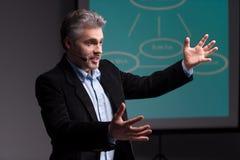 Entraîneur mûr faisant des gestes avant écran avec la présentation Photo stock