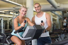Entraîneur masculin aidant la femme avec le vélo d'exercice au gymnase image stock