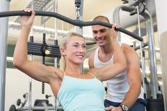Entraîneur masculin aidant la femme sur une machine de lat dans le gymnase photos stock