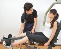 Entraîneur masculin Assisting de forme physique une jeune étudiante Doing Exer Photos stock