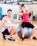Entraîneur masculin avec la femme faisant des craquements sur la boule Photos stock