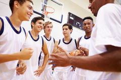 Entraîneur masculin de Team Having Team Talk With de basket-ball de lycée photographie stock libre de droits