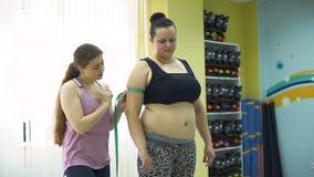 Entraîneur Measuring Arm de femme de poids excessif banque de vidéos