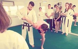 Entraîneur montrant la nouvelle prise de soumission dans la classe du Taekwondo photo libre de droits