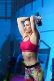 Entraîneur musculaire attirant puissant W de forme physique de femme orking  photographie stock