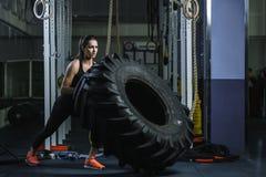 Entraîneur musculaire puissant de CrossFit de femme faisant la séance d'entraînement de pneu au gymnase photographie stock