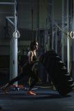 Entraîneur musculaire puissant de CrossFit de femme faisant la séance d'entraînement de pneu au gymnase photo libre de droits