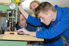 Entraîneur observant le conseil de perçage d'apprenti de travail du bois photos stock