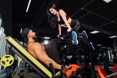Entraîneur personnel aidant des hommes établissant sur la machine de presse de jambe dans le gymnase Photo stock