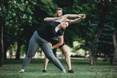 Entraîneur personnel aidant l'exercice obèse de femme photographie stock