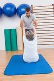 Entraîneur travaillant avec la femme supérieure sur le tapis d'exercice Photographie stock