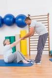 Entraîneur travaillant avec la femme supérieure sur le tapis d'exercice Images stock