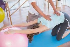 Entraîneur travaillant avec la femme sur la boule d'exercice image libre de droits